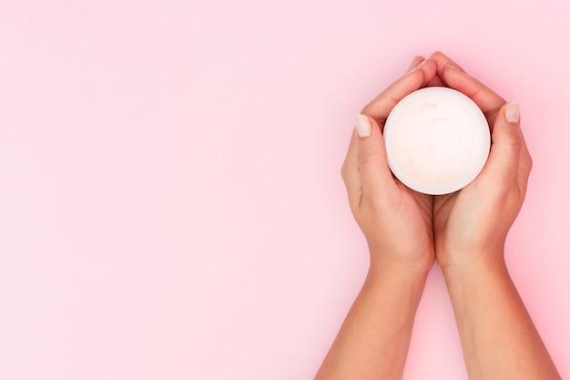 Femme Tenant Une Boîte De Crème Pour Le Visage Avec Espace Copie Photo gratuit