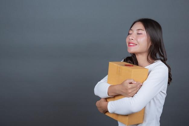 Femme tenant une boîte postale brune fait des gestes avec la langue des signes. Photo gratuit