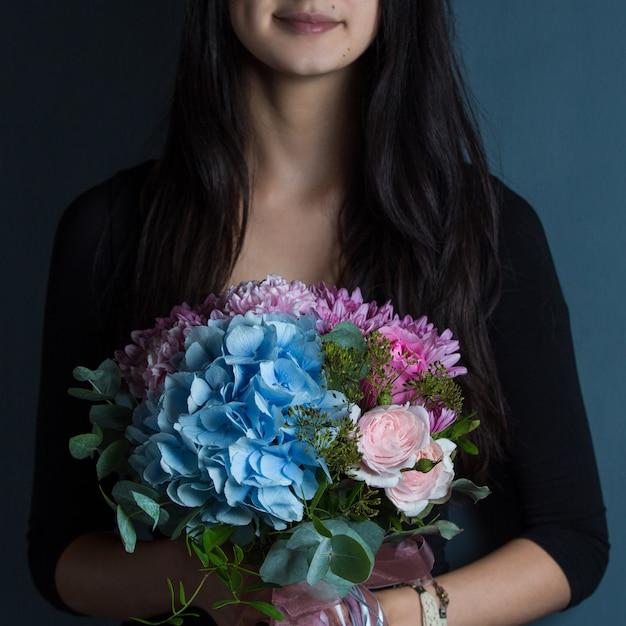 Une femme tenant un bouquet de fleurs à la main Photo gratuit
