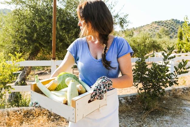 Femme tenant une caisse avec des légumes récoltés dans le champ Photo gratuit