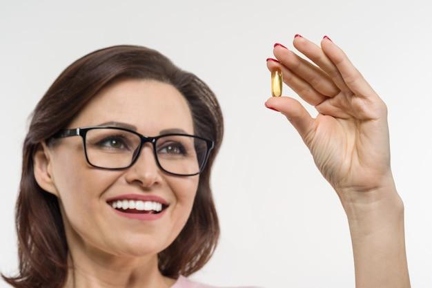 Femme tenant une capsule de vitamine e, huile de poisson Photo Premium