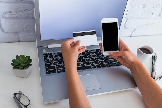 Femme tenant la carte de crédit et le téléphone mobile sur l'ordinateur portable sur le bureau Photo gratuit