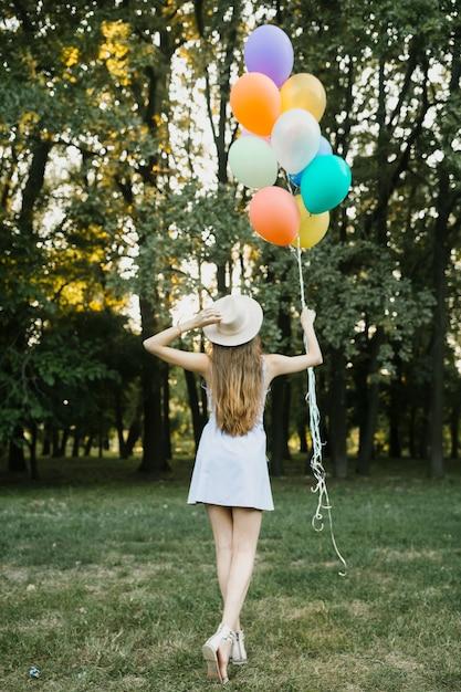 Femme tenant un chapeau et des ballons exterieurs Photo gratuit