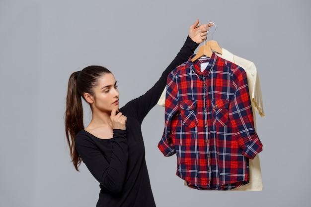 Femme Tenant Des Chemises, Choisir Quelle Tenue Porter Photo gratuit