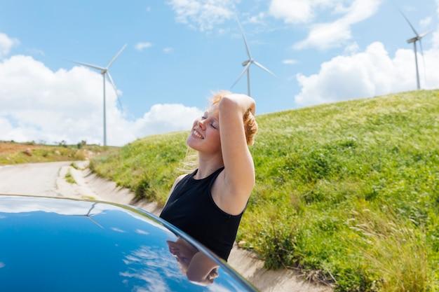 Femme tenant les cheveux et profiter du soleil par la fenêtre de la voiture Photo gratuit