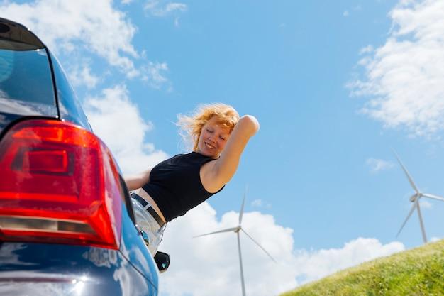 Femme tenant les cheveux et regardant par la fenêtre de la voiture Photo gratuit