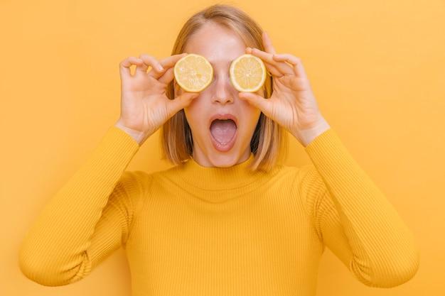 Femme tenant des citrons devant les yeux dans une scène jaune Photo gratuit