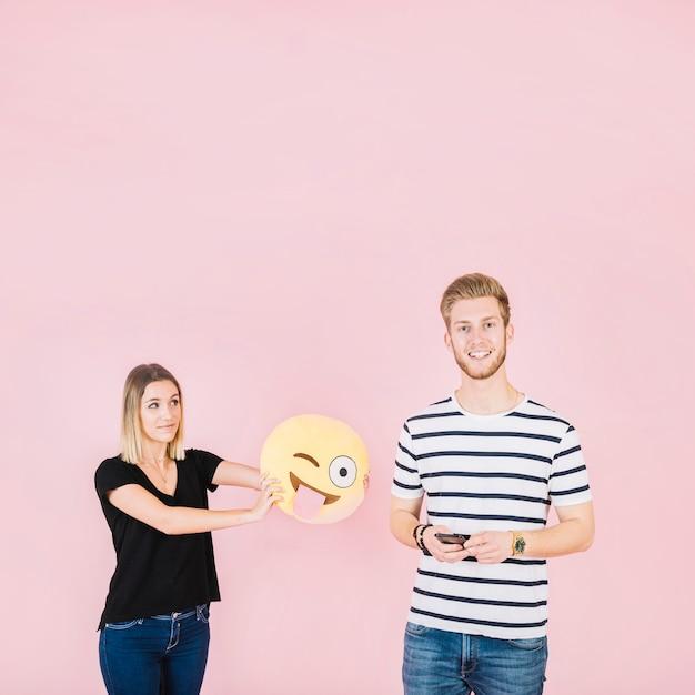 Femme tenant un clin d'œil emoji icône près d'un homme heureux avec téléphone portable Photo gratuit