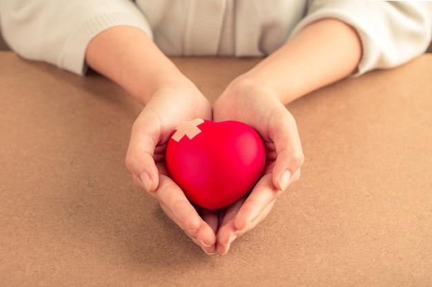Femme Tenant Un Coeur Rouge Avec Un Bandage Sur Fond En Bois. Concept De Soins De Santé. Photo Premium