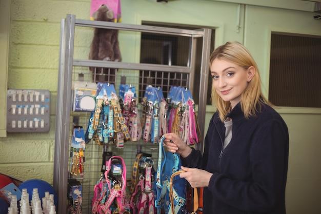 Femme Tenant Des Colliers De Chien En Boutique Photo gratuit