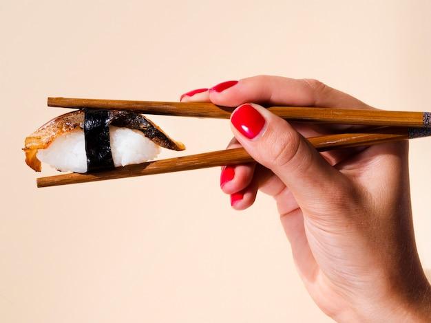 Femme tenant dans une paire de baguettes un sushi sur fond rose pâle Photo gratuit