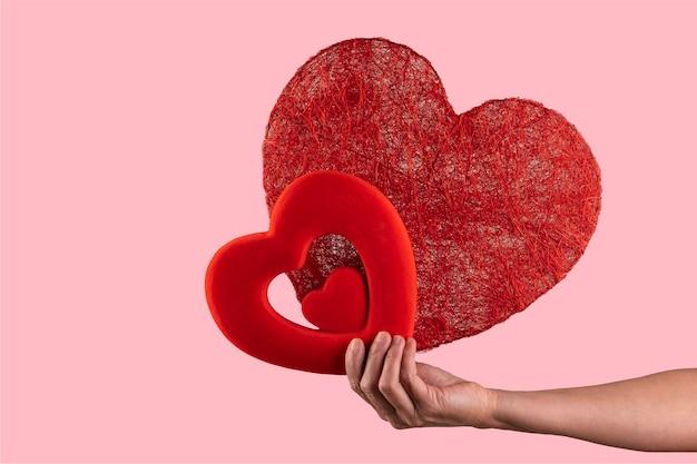 Femme Tenant Dans Ses Mains Deux Coeurs. Concept De La Saint-valentin Photo Premium