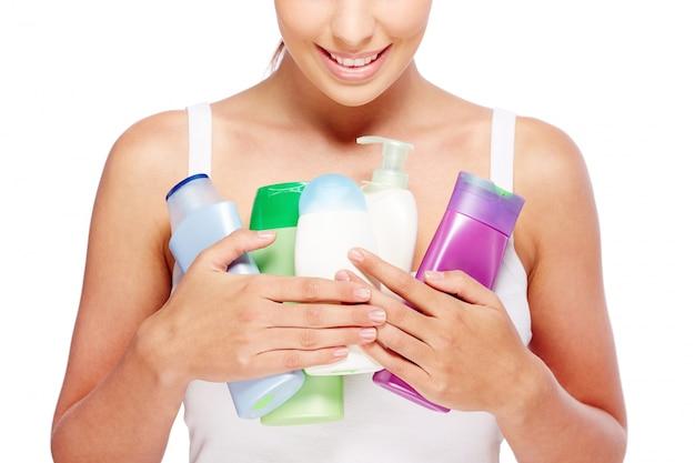 Femme tenant différentes lotions Photo gratuit