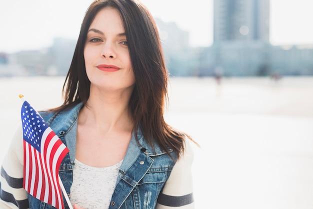 Femme tenant le drapeau américain en célébrant le 4 juillet à l'extérieur Photo gratuit