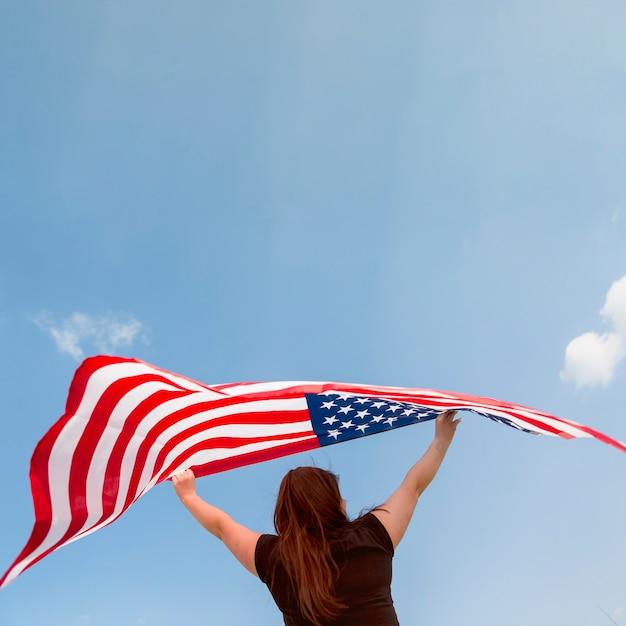 Femme tenant un drapeau américain Photo gratuit