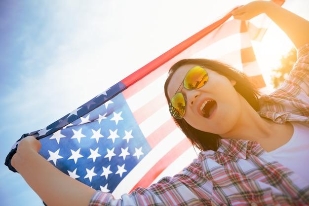 Femme tenant le drapeau des états-unis d'amérique et courir sur la plage. Photo Premium