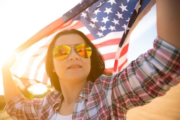 Femme tenant le drapeau des états-unis d'amérique sur la plage. Photo Premium