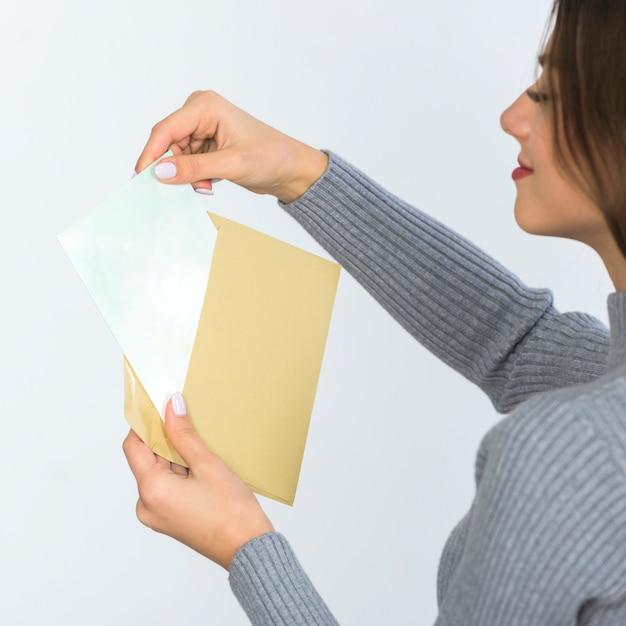 Femme tenant une enveloppe avec du papier vierge Photo gratuit