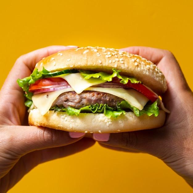 Femme tenant un hamburger à deux mains Photo gratuit