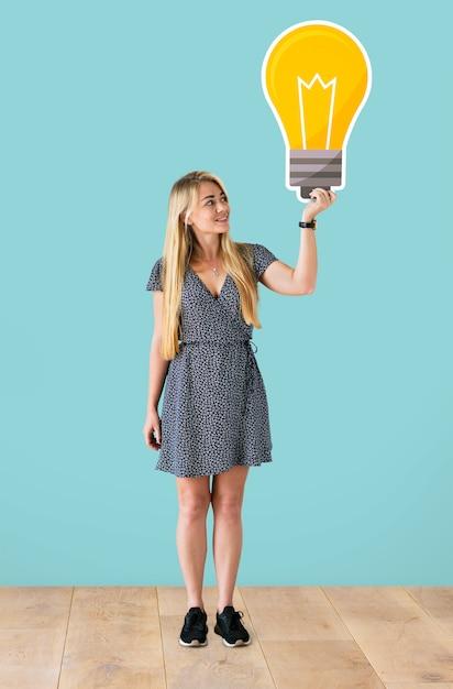 Femme tenant une icône d'ampoule Photo gratuit