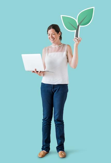 Femme tenant une icône de plante et utilisant un ordinateur portable Photo gratuit
