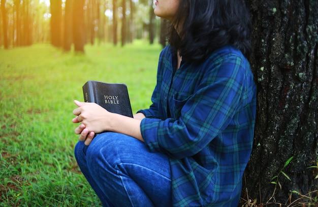 Femme tenant un livre, la bible, la nature. Photo Premium