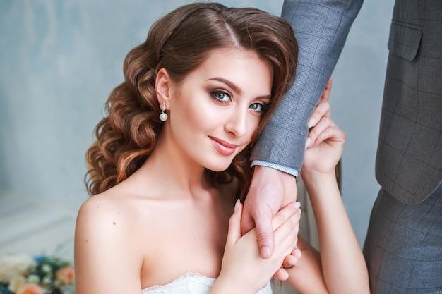Une femme tenant la main d'un homme. mariée en robe et marié Photo Premium