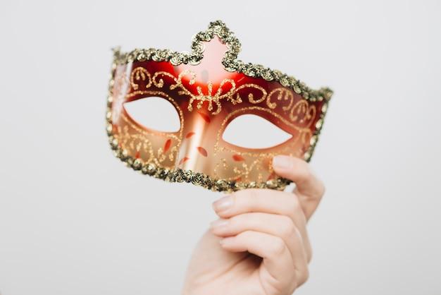 Femme tenant un masque de carnaval rouge à la main Photo gratuit