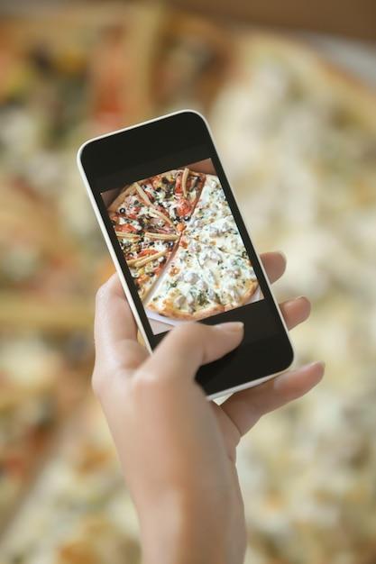 Femme tenant une photo de pizza Photo gratuit
