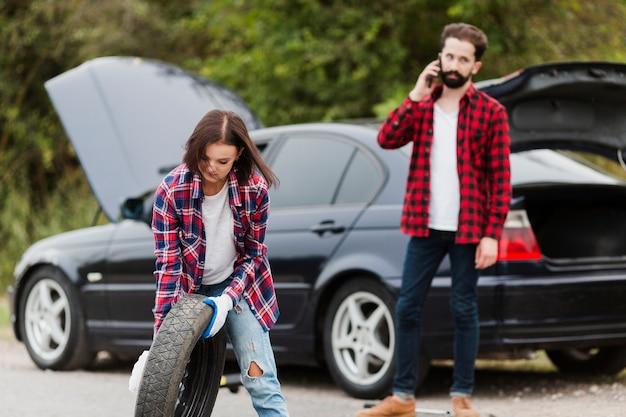 Femme tenant un pneu de secours et homme parlant au téléphone Photo gratuit