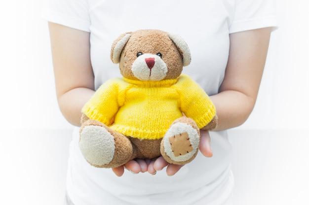 Femme tenant et protégeant un ourson en peluche brun portant des chemises jaunes assis sur un fond blanc, symbole de l'amour ou de rencontres amoureuses Photo Premium
