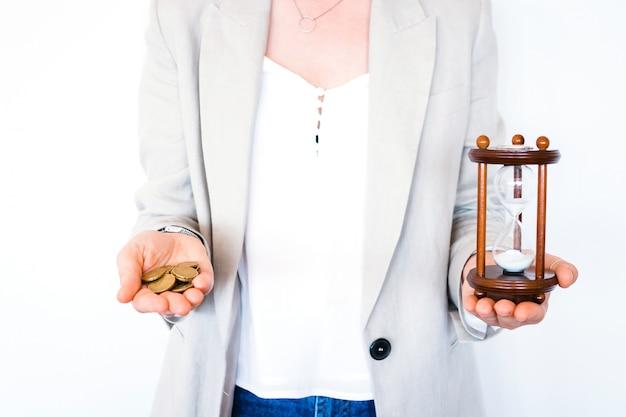 Femme tenant le sablier et pièces isolés sur fond blanc. investissement de temps et épargne retraite. compte à rebours d'urgence pour le concept de délai d'affaires. le temps, c'est de l'argent Photo Premium