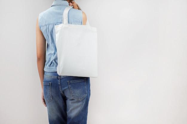 Femme tenant un sac en tissu écologique isoler sur fond gris Photo Premium