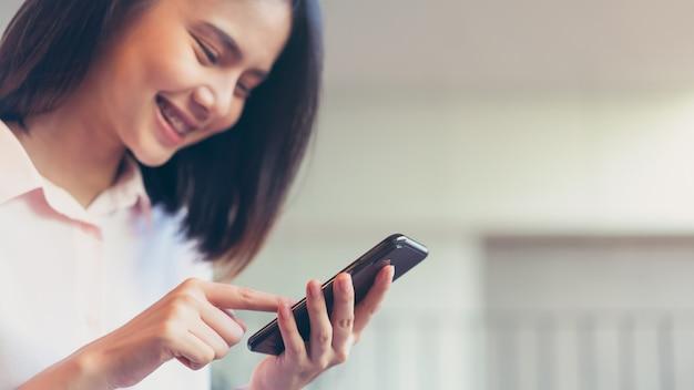 Femme tenant un smartphone, maquette d'écran vide. en utilisant un téléphone portable au café. Photo Premium