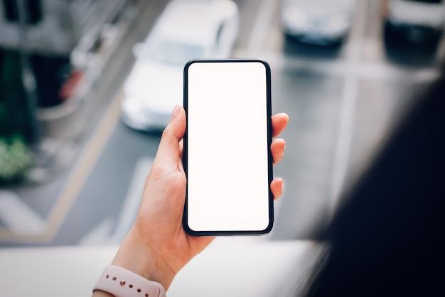 Femme tenant un smartphone. en utilisant un téléphone portable sur le style de vie. Photo Premium