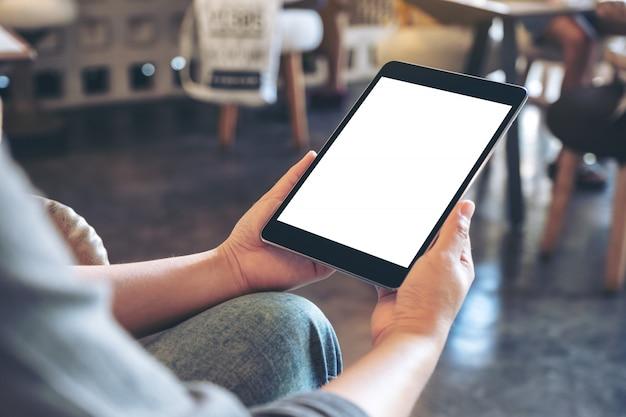Une Femme Tenant Un Tablet Pc Noir Avec écran Blanc Vide Alors Qu'il était Assis Dans Un Café Photo Premium