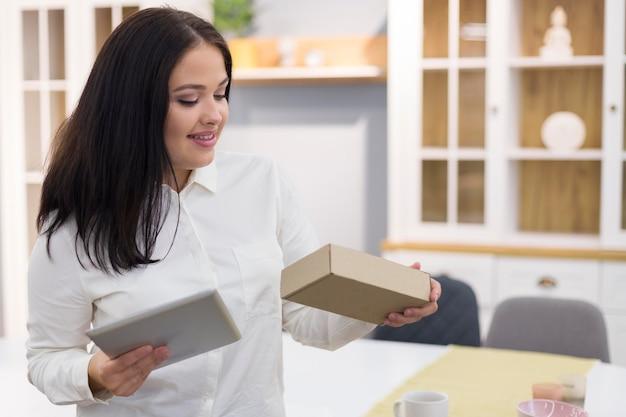 Femme Tenant Une Tablette Et Une Boîte Photo Premium