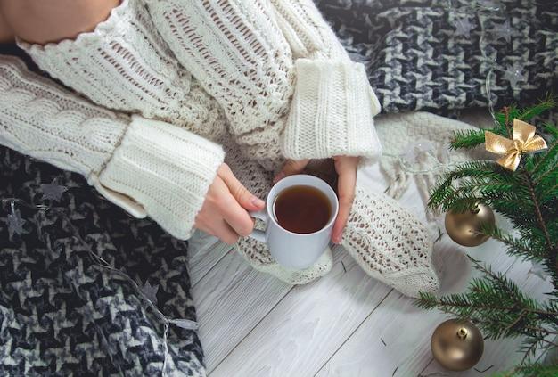Femme tenant une tasse de thé à côté de ses jambes Photo Premium
