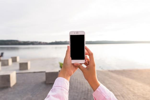 Femme tenant le téléphone mobile en face du lac idyllique Photo gratuit