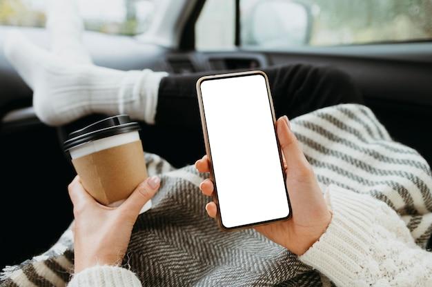 Femme Tenant Un Téléphone Vierge Et Une Tasse De Café Photo gratuit