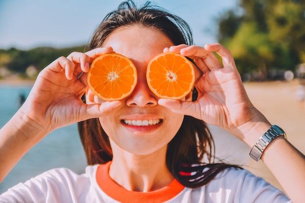 Femme tenant une tranche d'orange au fond de la mer de plage, fond vintage de vacances d'été Photo Premium