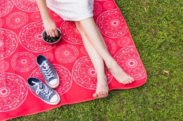 Femme tenir la cerise à la main sur une couverture rouge sur l'herbe verte Photo gratuit