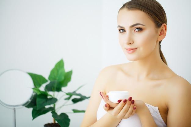 Femme tenir la crème cosmétique, beau visage jeune mannequin, Photo Premium