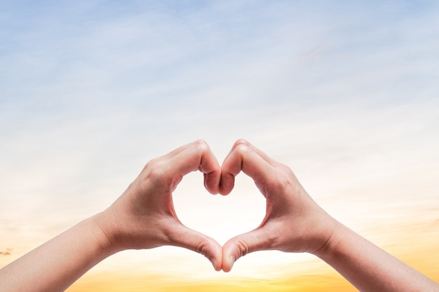 Femme Tenir La Main Vers Le Ciel En Forme De Coeur D'amour Sur La Lumière Du Soleil Flare Et Nuage Avec Ciel Clair Photo Premium