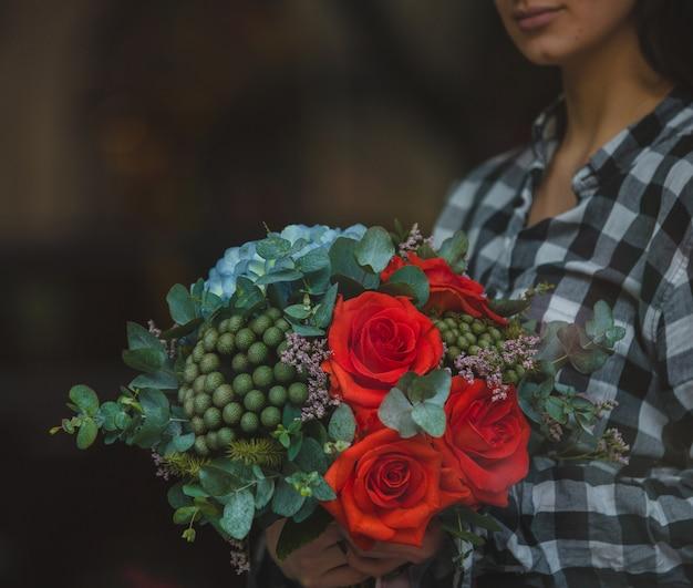A, femme, tenue, bouquet, roses rouges, velours, et, fleurs vertes, main, rue Photo gratuit