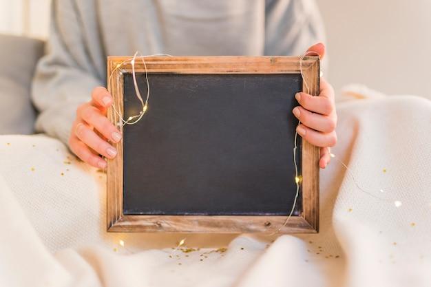 Femme, tenue, cadre photo, à, guirlandes lumières Photo gratuit