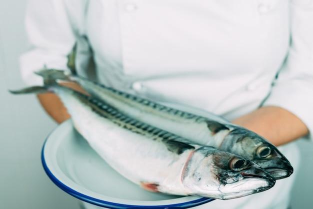 Femme En Tenue De Chef Montrant Un Plat Avec Du Poisson Frais. Concept De Cuisine. Maquereau Frais Sur Une Plaque Blanche. Photo Premium