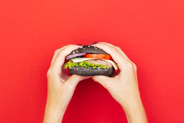 Femme, tenue, hamburger, table rouge Photo gratuit