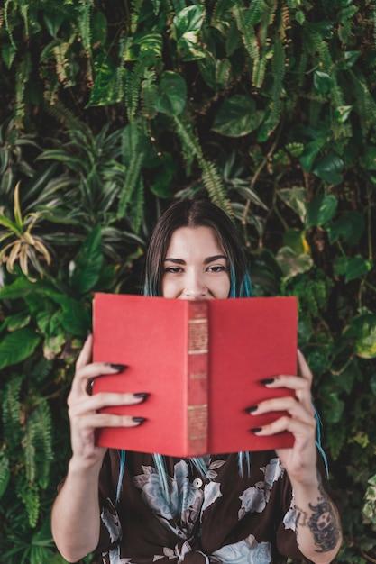 Femme, tenue, livre, devant, bouche, debout, contre, plante Photo gratuit