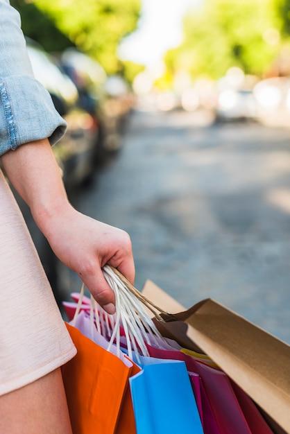 Femme, tenue, lumineux, sacs provisions, dans main Photo gratuit